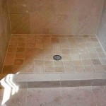 Hand cut and installed travetine tiles give this shower an old world appearance